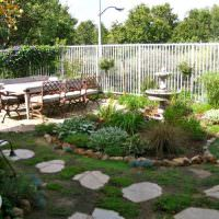 Обеденный стол перед садовым фонтанчиком
