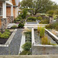 Водоем с растениями в палисаднике загородного дома