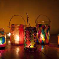 Горящие свечи внутри сувенирных банок
