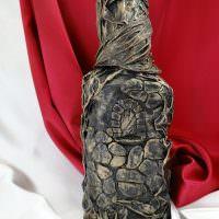 Декоративная бутылка на фоне красного материала