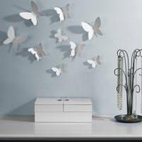 Бабочки из белой бумаги на голубой стене