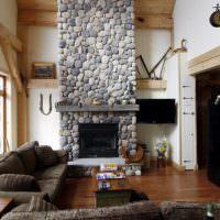 Камин из бутового камня в гостиной с высоким потолком