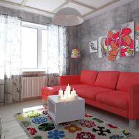 Красный диван в комнате с серыми стенами