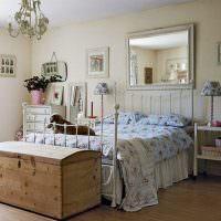Деревянный сундук перед кроватью с кованным каркасом