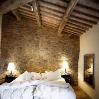 Белая кровать в спальне с деревянным потолком