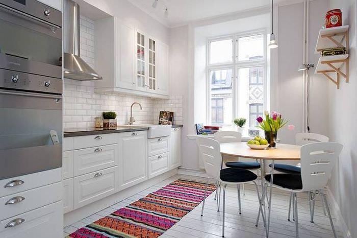 Пестрый коврик в интерьере белой кухни