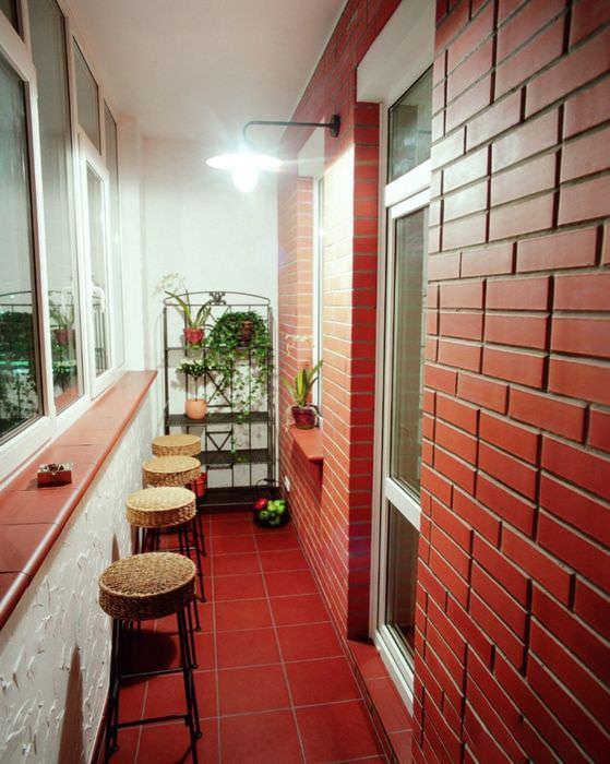 Красивый балкон с кирпичной стеной красного цвета