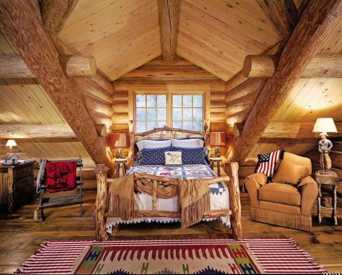 Кровать из грубого дерева в мансарде загородного дома