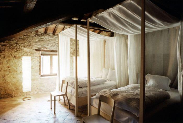 Кровати с простыми балдахинами в комнате с каменными стенами