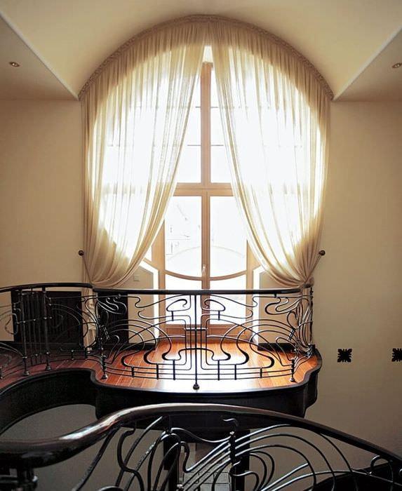 Круглое окно с дверью на балкон частного дома