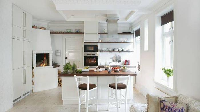 Интерьер белой кухни с камином