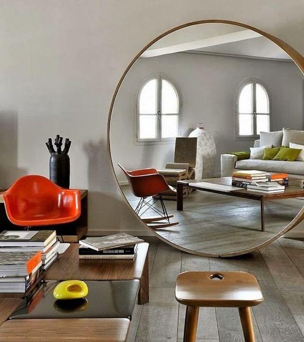 Большое круглое зеркало на полу гостиной