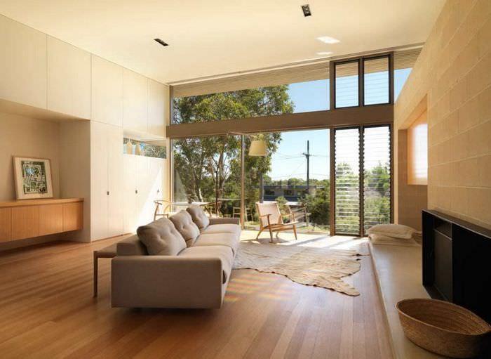 Интерьер бежевой гостиной с панорамным окном