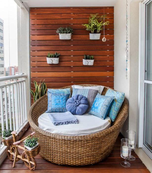 Плетенное кресло на деревянном полу открытого балкона