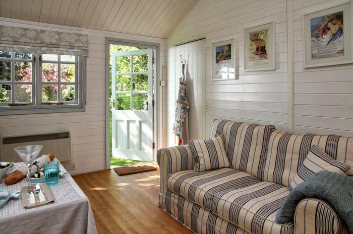 Диван с полосатой обивкой в комнате небольшого дачного домика