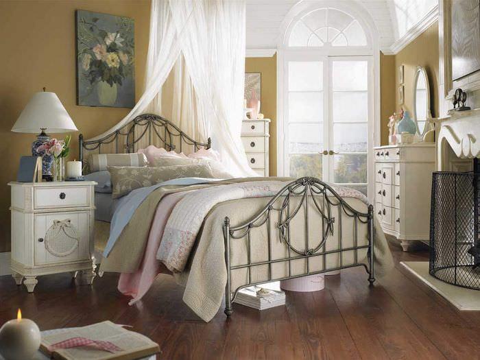 Винтажная тумбочка около кровати на металлическом каркасе
