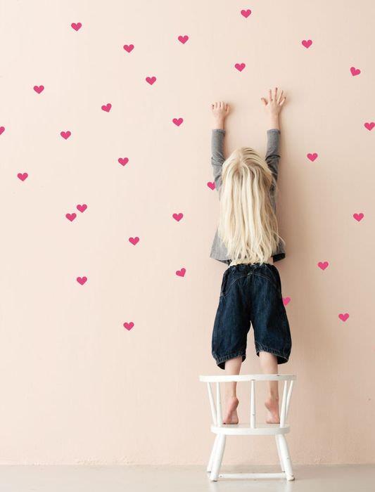 Украшение розовой стены красными сердечками