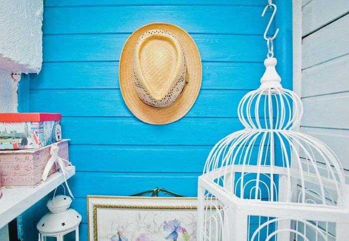 Светло-коричневая шляпа на синей стене балкона