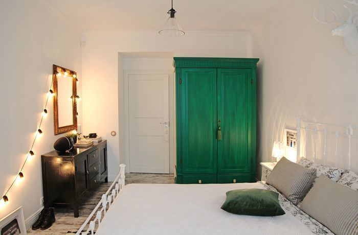 Интерьер светлой спальни с зеленым шкафом