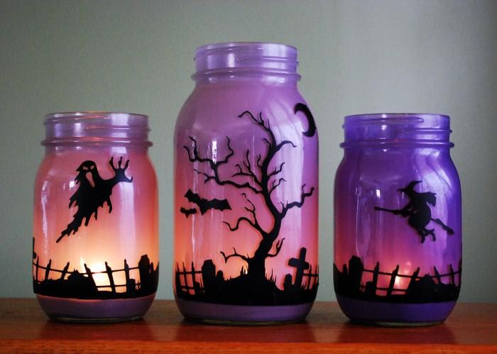 Раскрашенные стеклянные банки с горящими свечами внутри