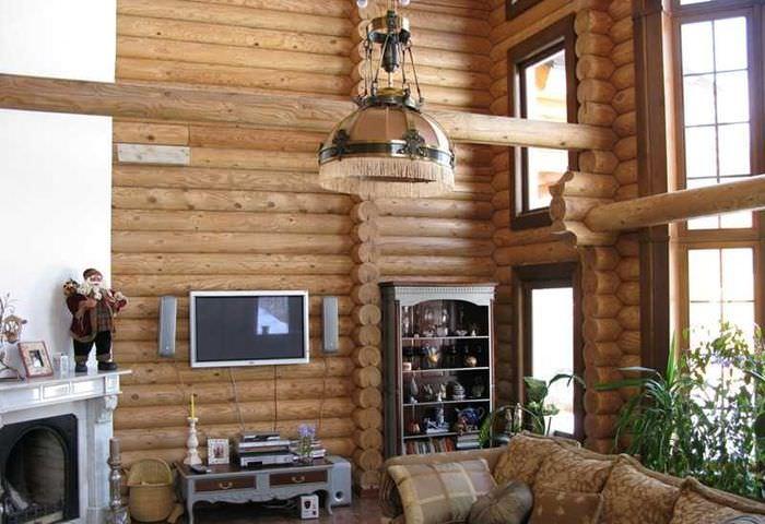 Светильник с большим блестящим плафоном в гостиной дома из бревна