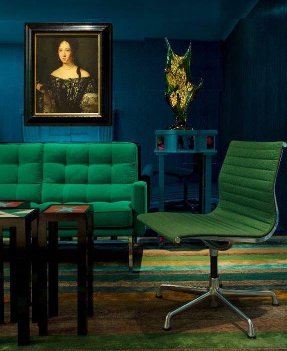 Зеленая мебель на фоне темно-синих стен гостиной комнаты