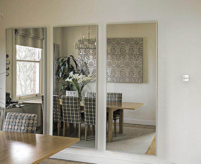 Три зеркала без рам на стене кухни-столовой