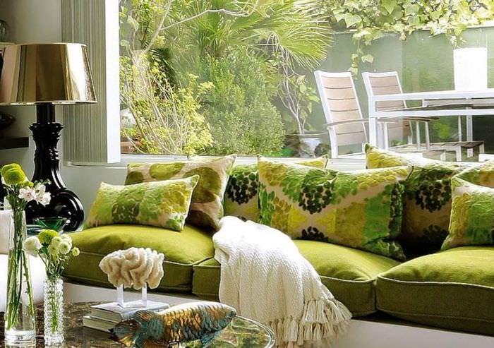Зеленый диван перед окном гостиной в частном доме