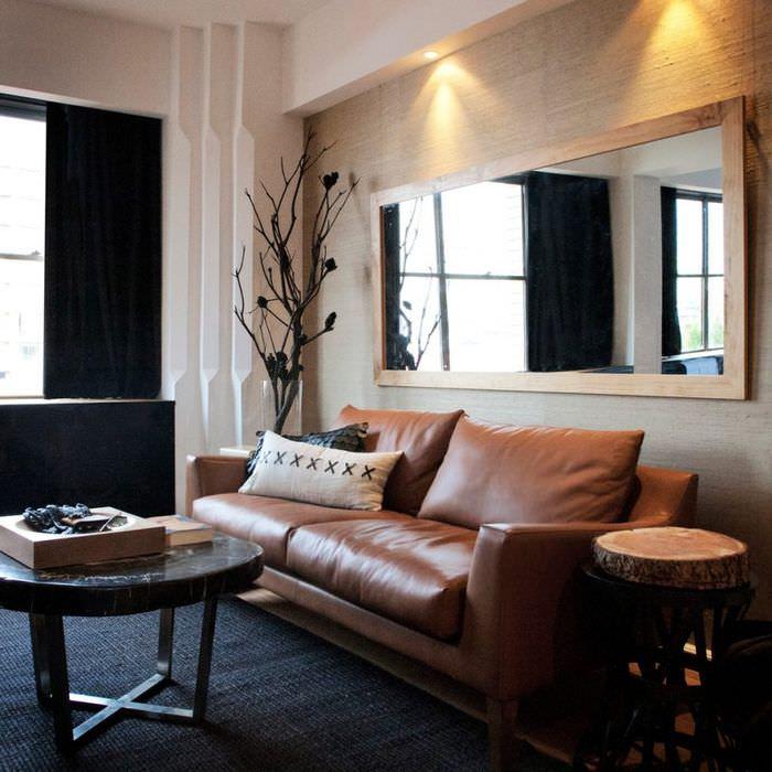 Большое зеркало над кожаным диваном в гостиной