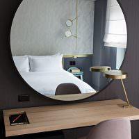 Большое зеркало на черной стене