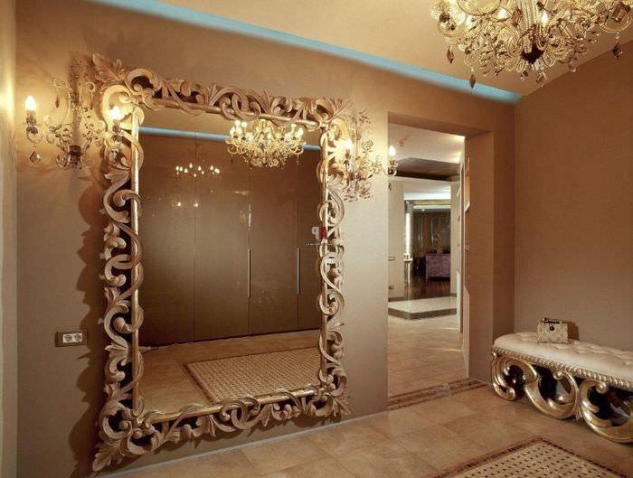 Зеркало в раме с завитушками на стене прихожей