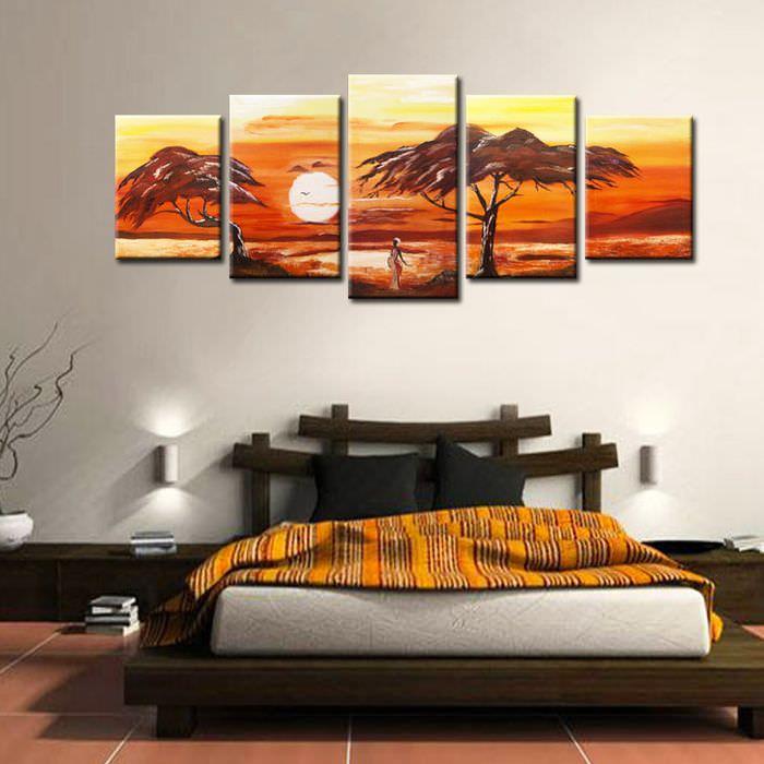 Низкая кровать в спальне с картинами на стене