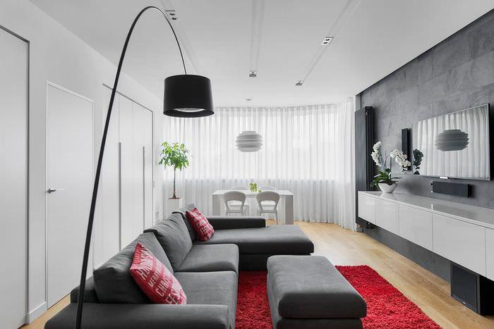 Серый диван на бардовом ковре в гостиной