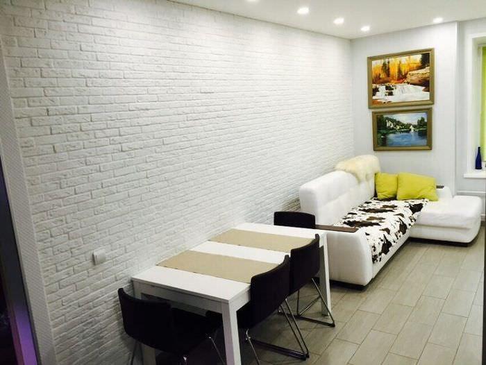 Белая кирпичная стена в интерьере кухни-гостиной
