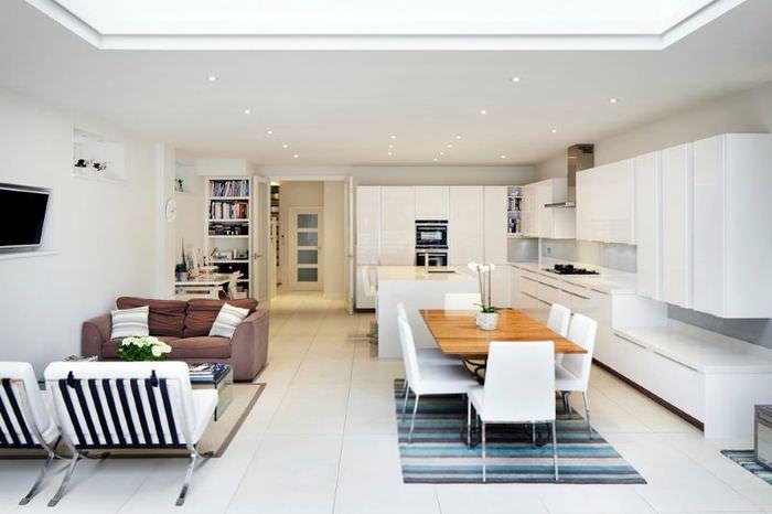 Дизайн просторной кухни-гостиной с белым гарнитуром