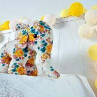 Игрушка-слоник на детской кровати