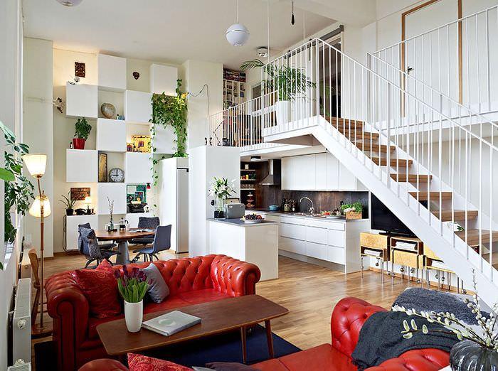 Белая лестница в гостиной с красными диванами