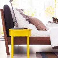 Желтый стул перед кроватью в спальне