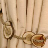 Веревочка с деревянными спилами на бежевой занавеске
