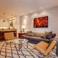 Серый диван у кирпичной стены