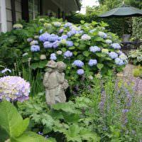 Садовая скульптура на фоне гортензии с сиреневыми цветками