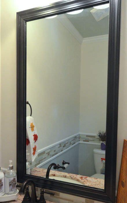 Черная рамка из плинтуса на зеркале в ванной комнате
