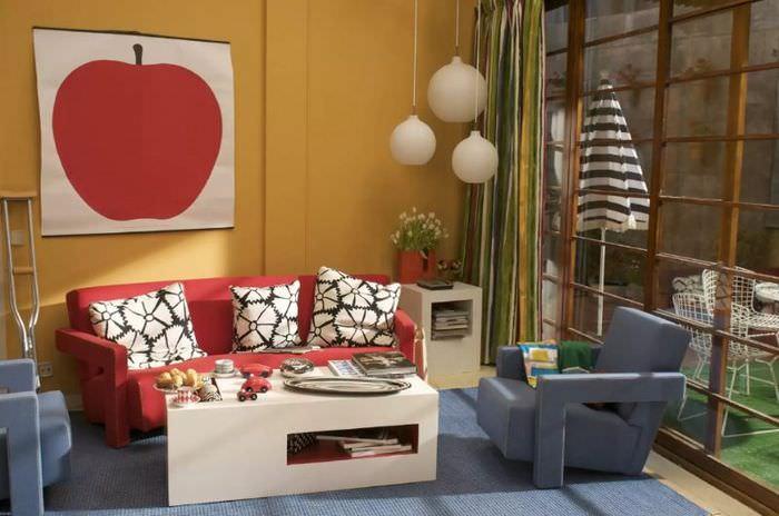 Картина с большим яблоком на оранжевой стене гостиной