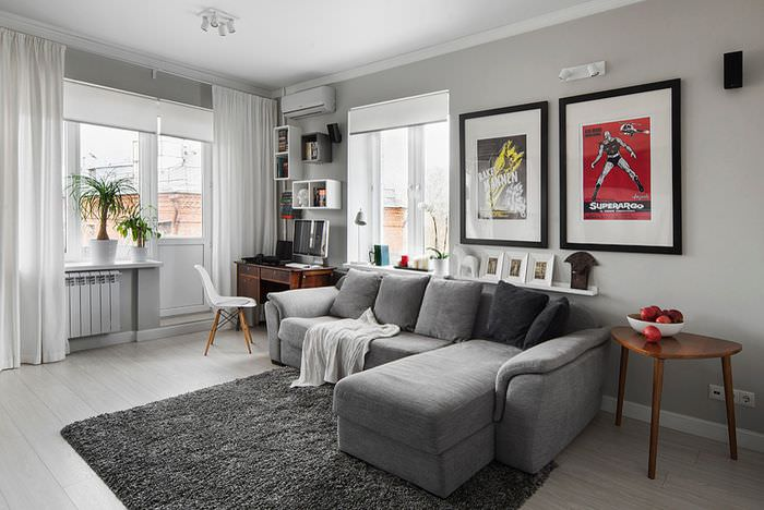Две картина над серым диваном в угловой гостиной