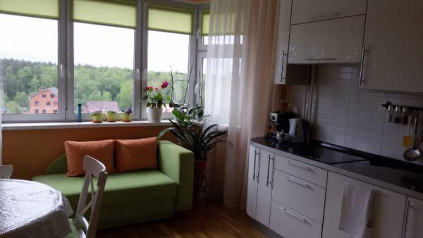 Зеленый диванчик перед окном кухни