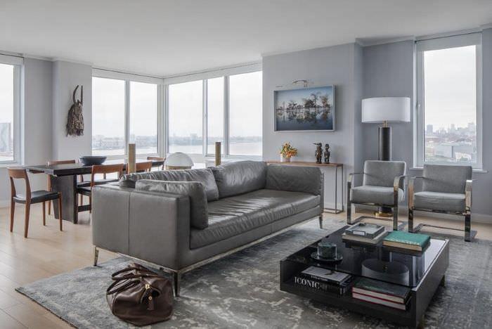 Интерьер гостиной с серым диваном посередине