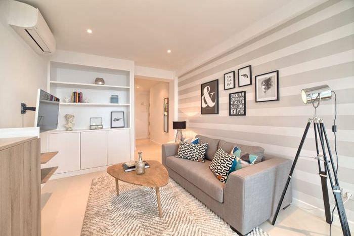 Серый диван прямой конфигурации в комнате с полосатыми обоями