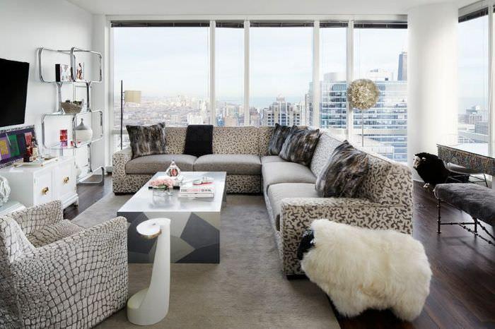 Диван с подушками серого и бежевого цветов в гостиной с большими окнами
