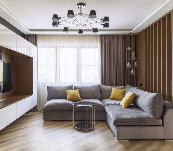Серый диван угловой формы в интерьере гостиной