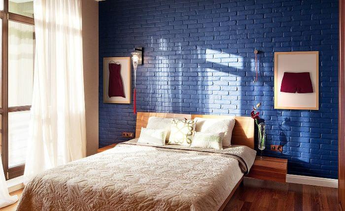 Двухспальная кровать в комнате с синей кирпичной стеной